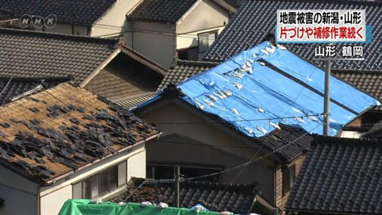 Workers using sheets to cover quake-damaged roofs