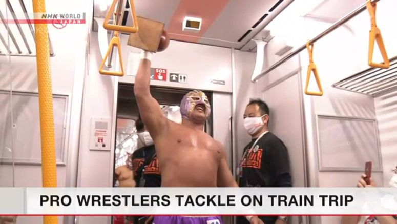 Pro wrestlers perform on a train
