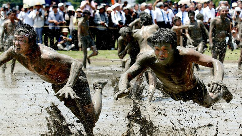 Men get dirty as part of Mie's famous rice-planting festival