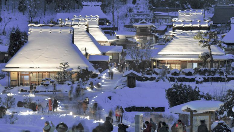 Houses with thatched roofs covered in snow are being lit up with lanterns for a special event at Kayabukinosato