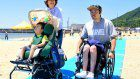 Wheelchair-user rolls out a road to the waves on Kobe beach